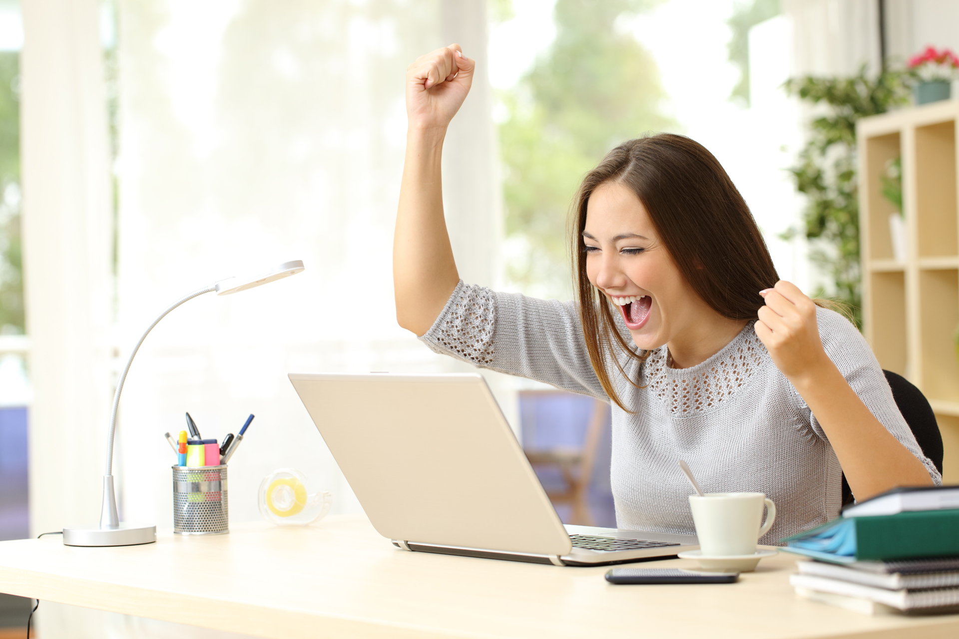 A woman watching a laptop on a desk winning at home