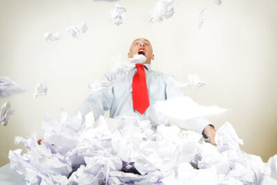 A stressed out businessman being buried by papers.