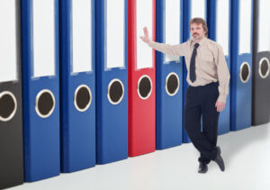 Man leaning against business archive folders - keeping data safe concept
